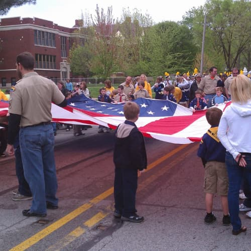 People stretching out an American Flag at a parade
