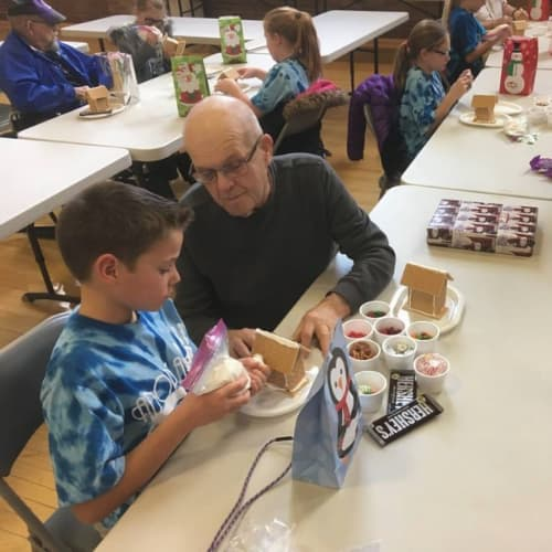 Young child with a grandparent decorating gingerbread houses