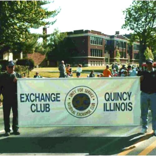 Exchange Club sign being held by two men at a parade