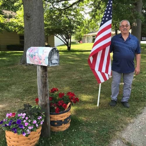 Man holding an American flag in front yard